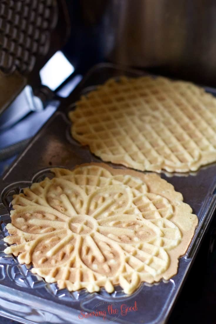 cooked pizzelle cookies in the cookie iron