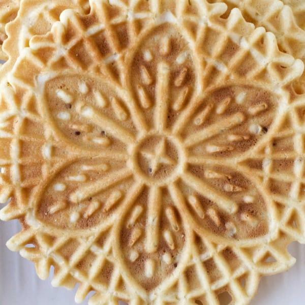 vertical image of lemon pizzelle italian cookies