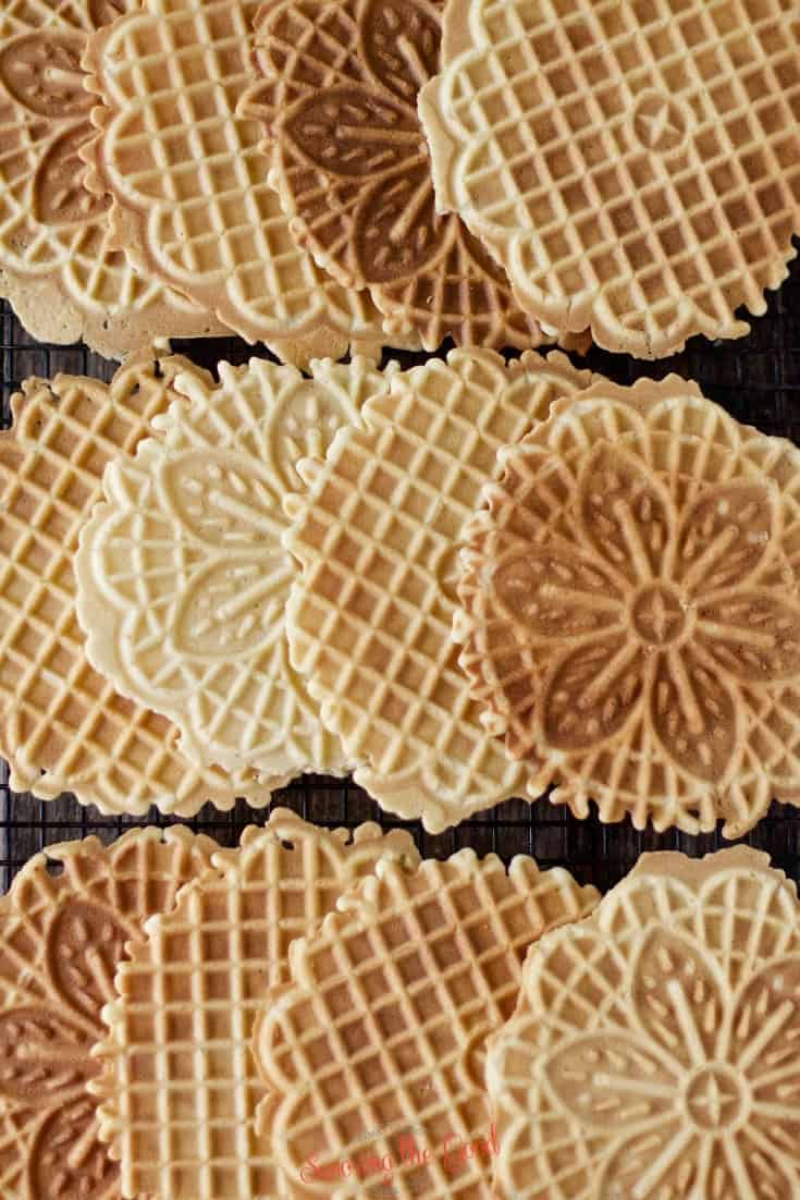 lemon pizzelle cookies of different doneness on the cooking rack