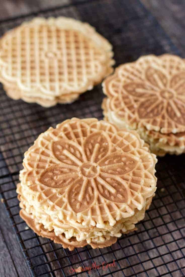 3 stacks of lemon pizzelle cookies on a cooling rack