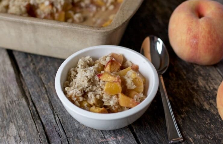 horizontal image of peach crisp in a white bowl.
