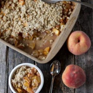 delicious peach crisp recipe with extra peaches for garnish