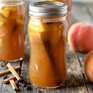 horizontal image of peach moonshine in a glass quart jar