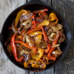 horizontal image of sous vide fajita vegetables in a cast iron pan