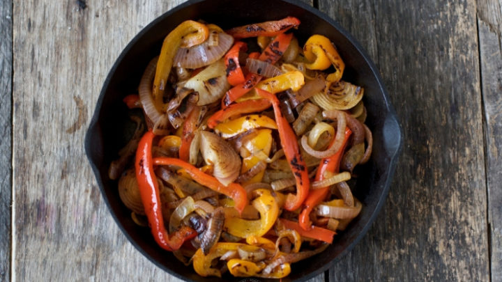 horizontal image of sous vide fajita vegetables in a cast iron pan
