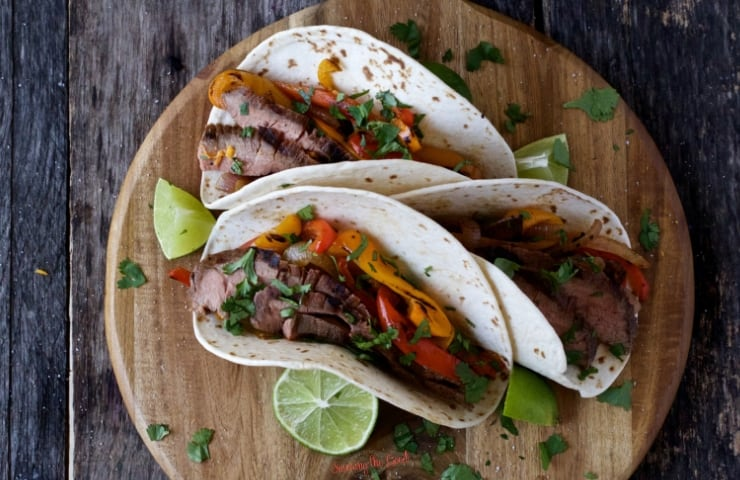3 sous vide flank steak fajita tacos on a round wooden cutting board