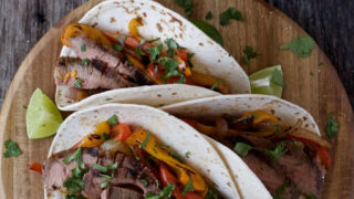 3 sous vide flank steak tacos on a round cutting board