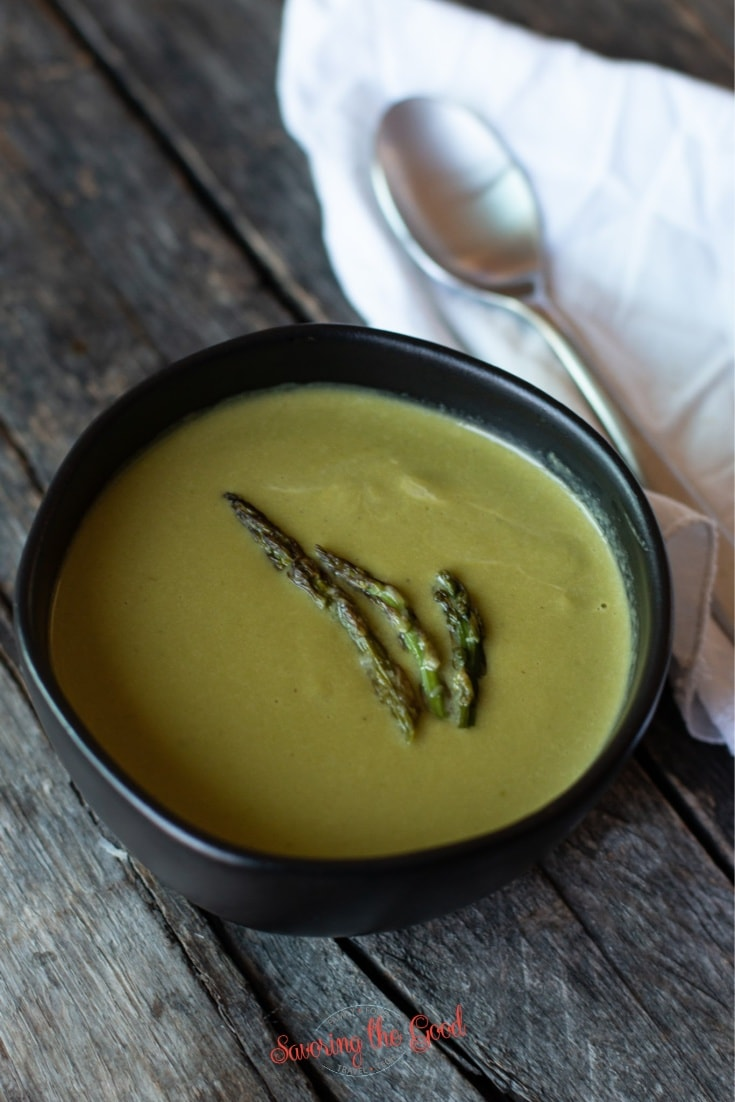Cream of asparagus soup in a black bowl