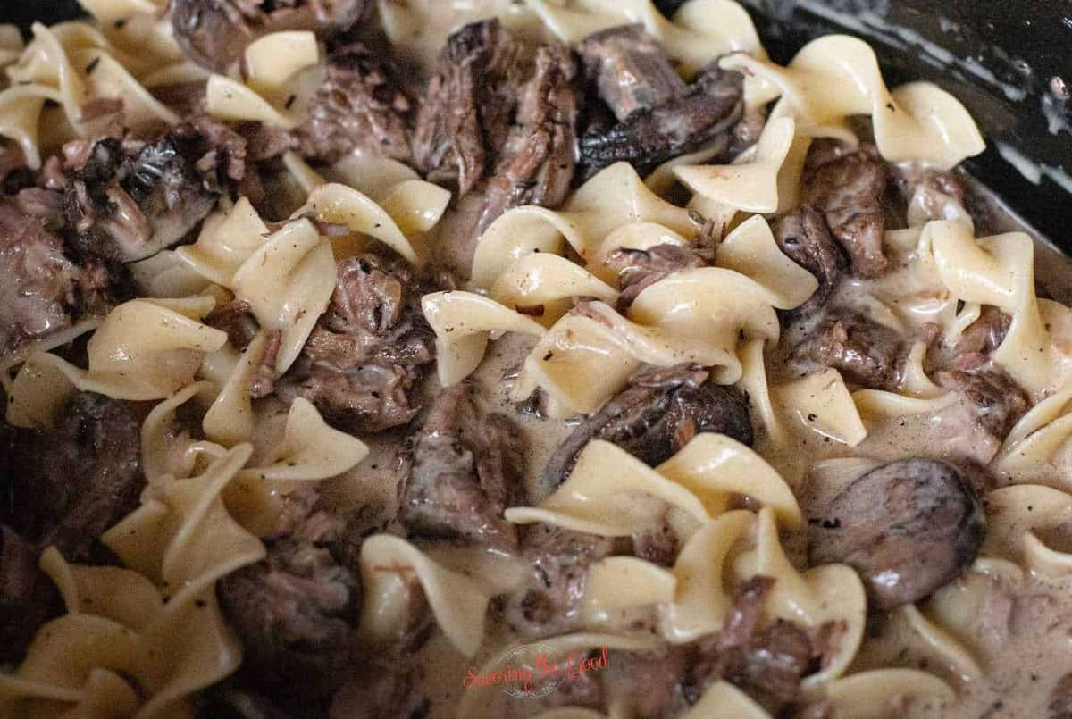 close shot of the beef stroganoff with the noodles added to the crockpot.