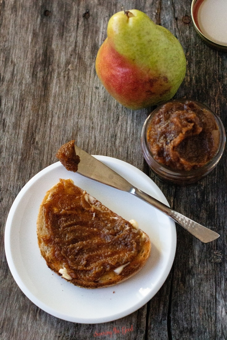 pear butter on buttered toast on a white plate with a jar and a spreading knife