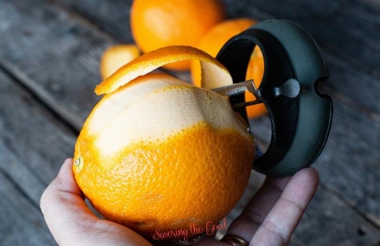 peeling the peel off of an orange with a vegetable peeler