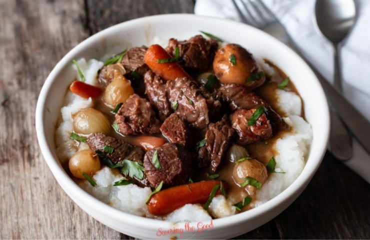 Sous Vide Guinness Beef Stew served over mashed potatoes in a white bowl, horizontal image