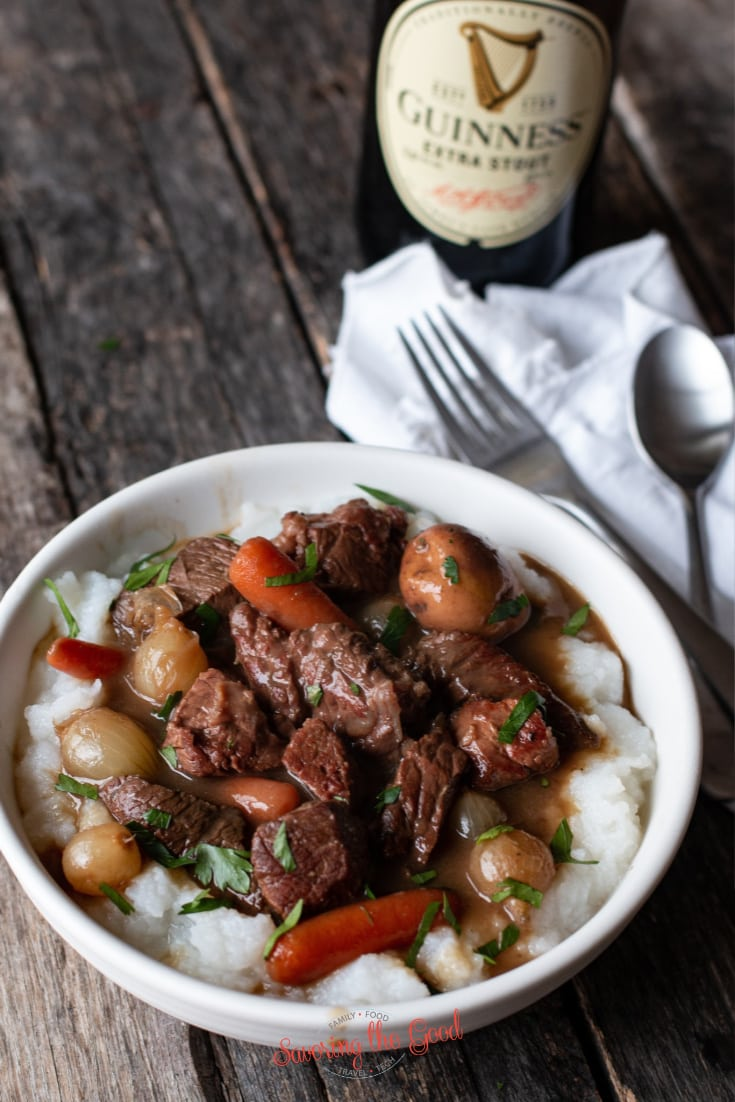 Guinness Beef Stew on a bed of mashed potatoes in a white bowl