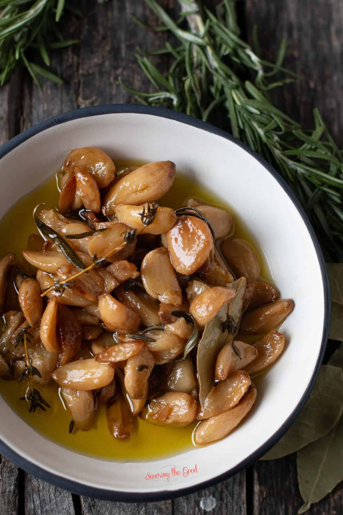 beautifully colored garlic confit in a white bowl with rosemary as garnish, vertical image
