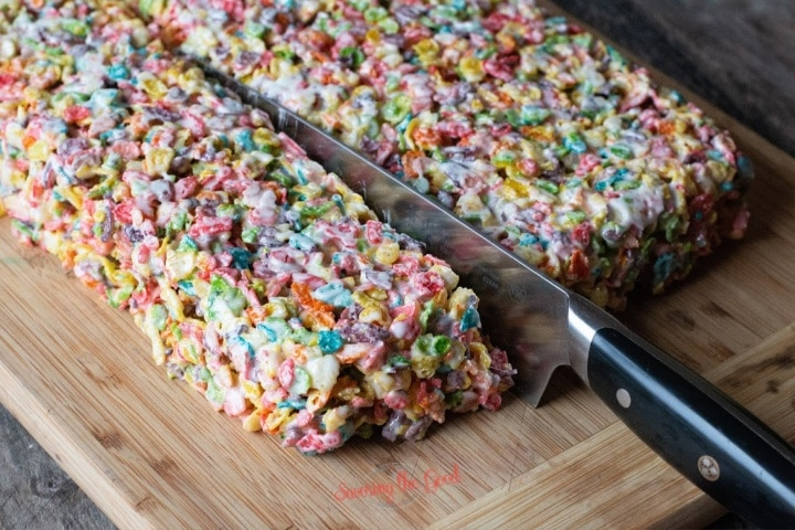 fruity pebbles treats being sliced with a knife