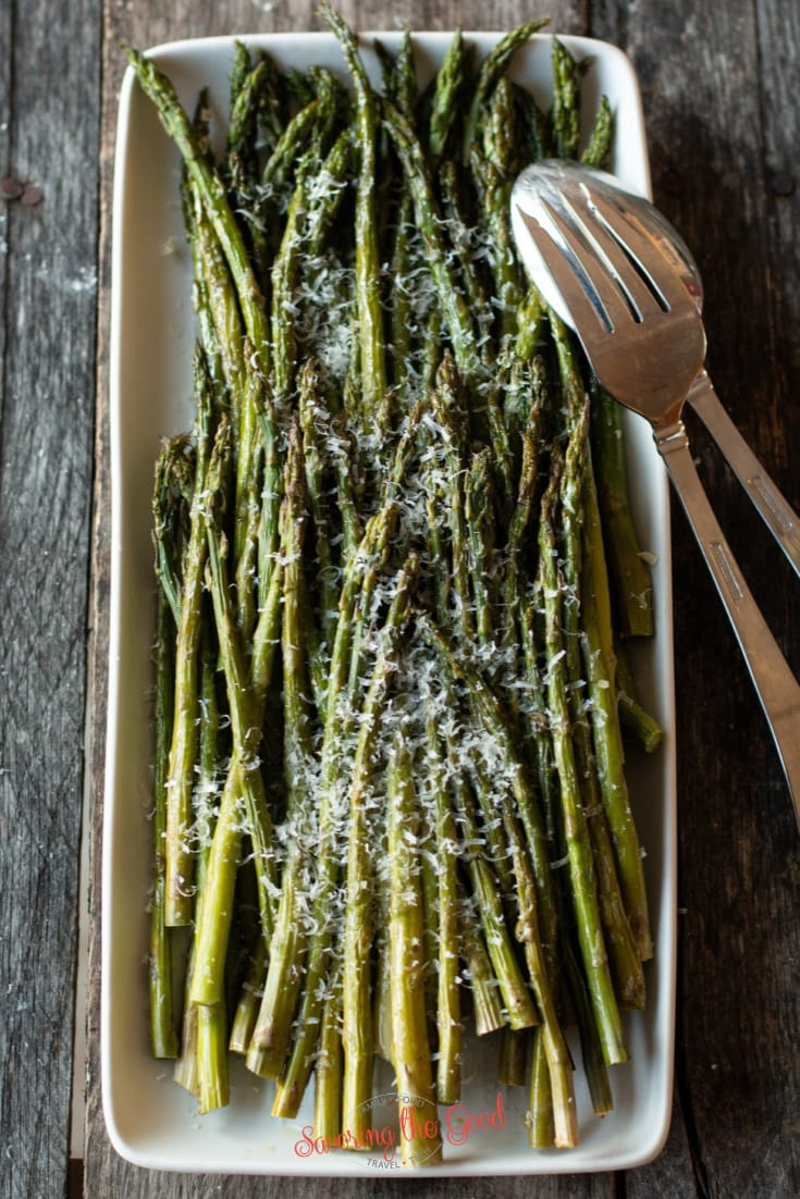 oven roasted asparagus on a shite rectangle serving platter with serving fork and spoon