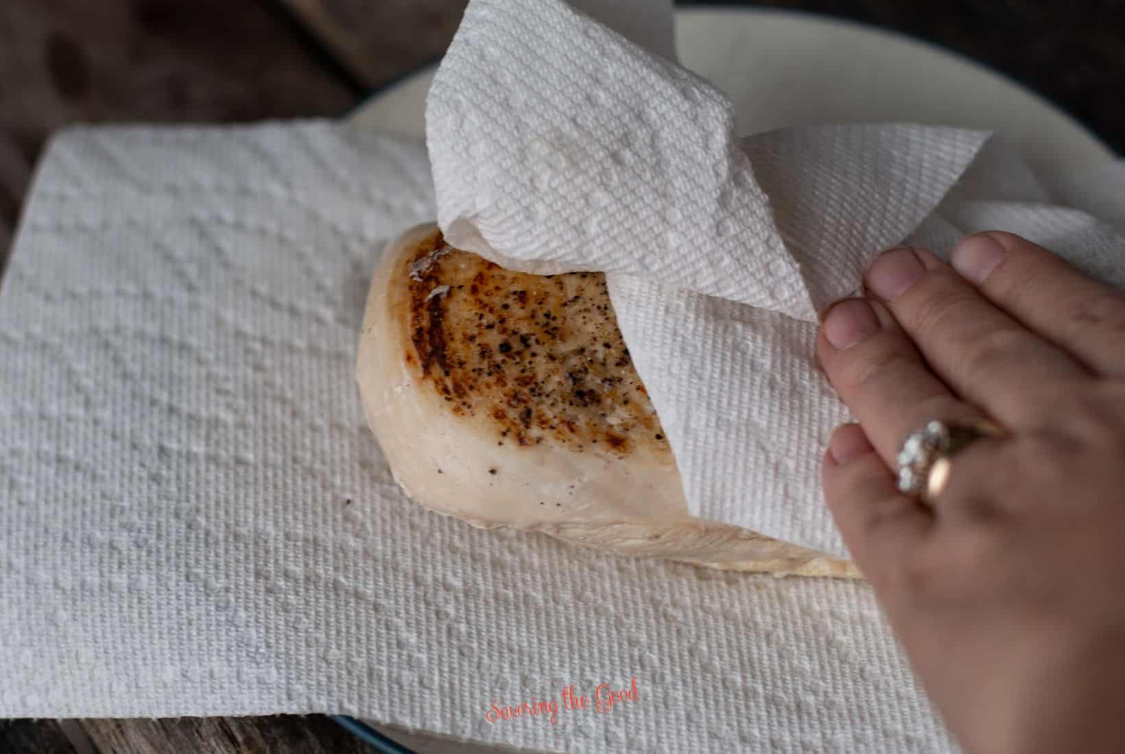 patting a sous vide chicken breast dry with a paper towel after cooking in preparation of searing