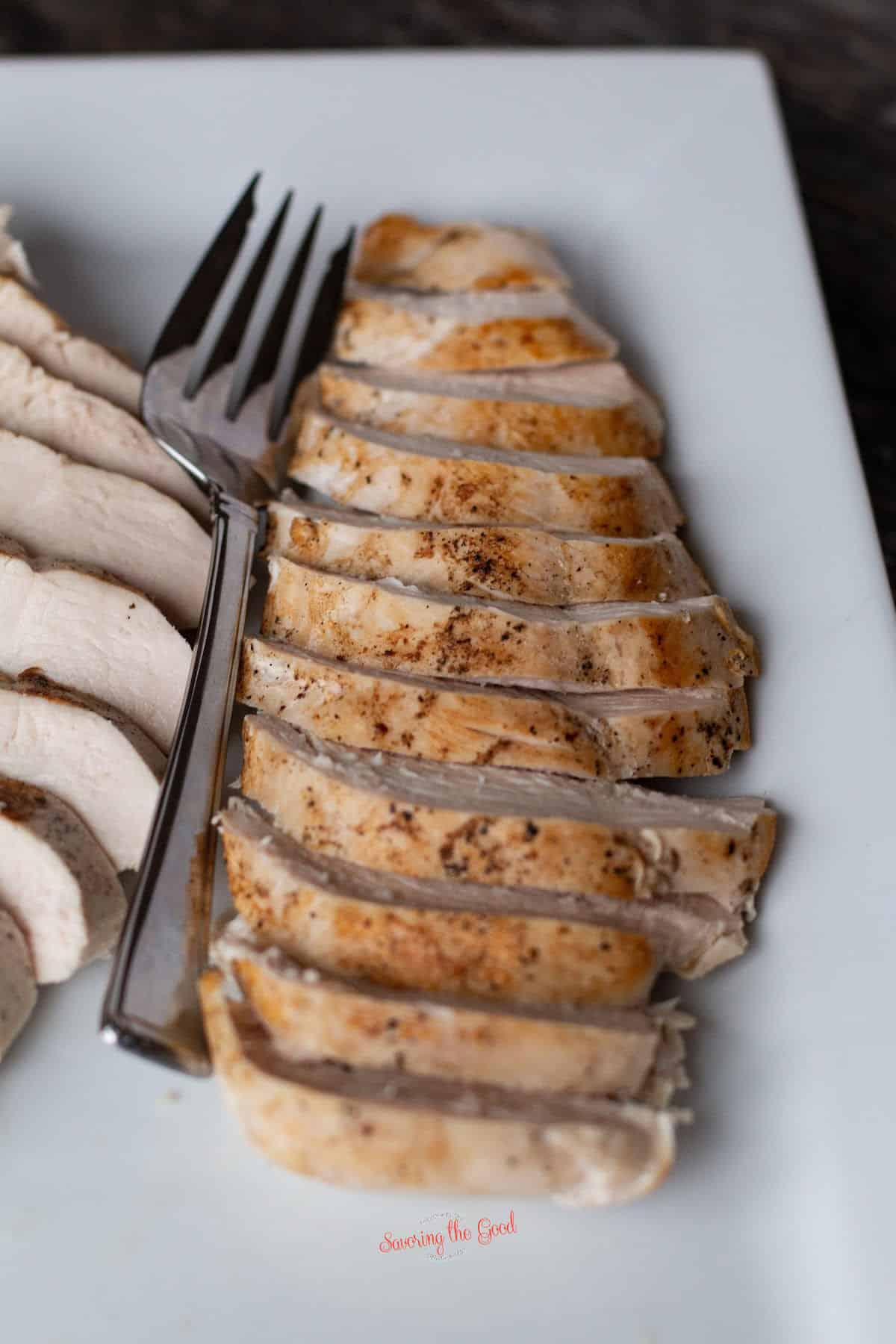 sous vide chicken breast sliced on a white rectangle serving plate with a serving fork