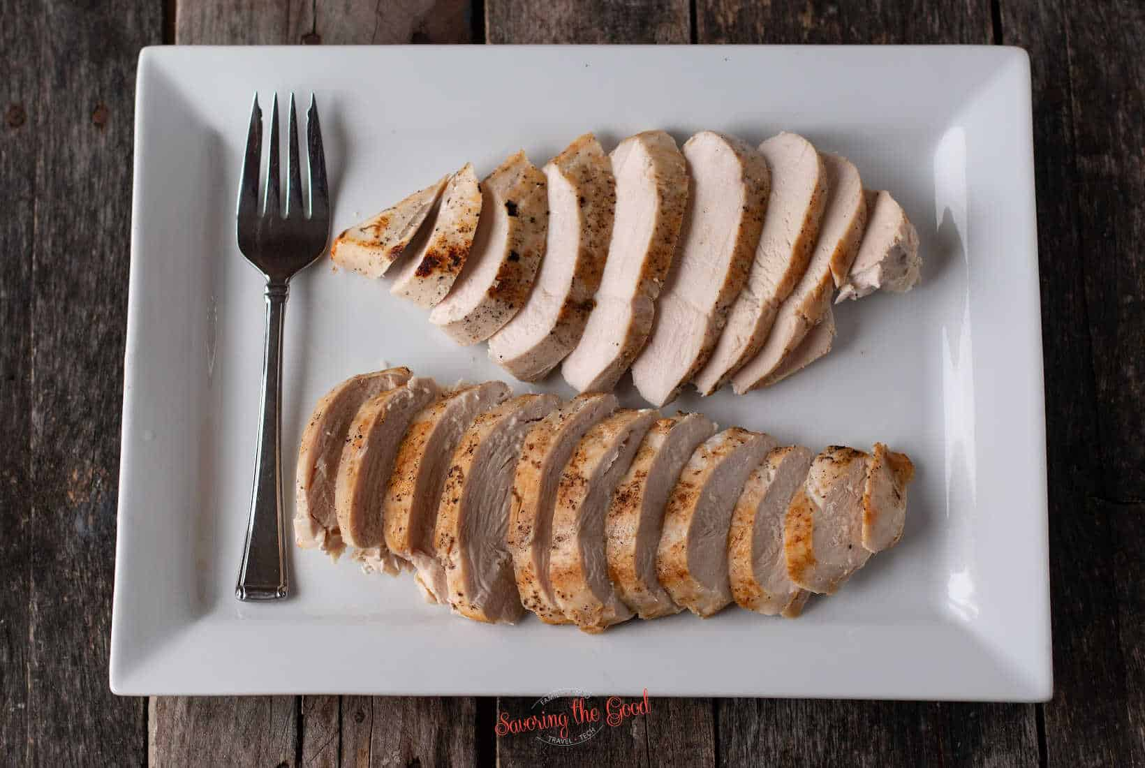 2 sous vide chicken breasts sliced and fanned out on a white rectangle serving plate