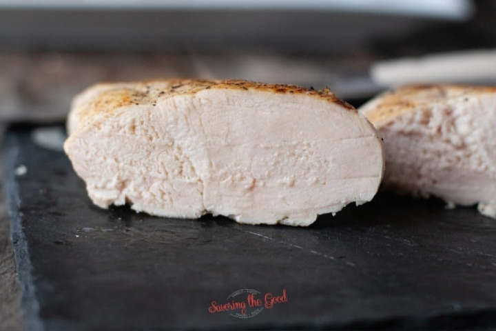 sous vide chicken breast sliced open to see the moisture and texture on a dark surface, horizontal image