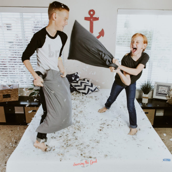 2 kids having a pillow fight on a bed, feathers coming out of the pillows