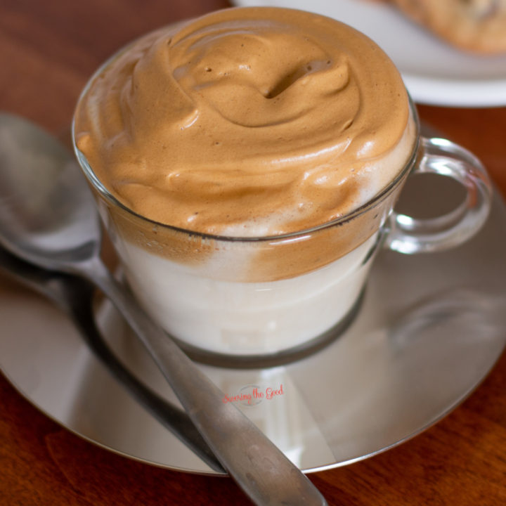 whipped coffee in a glass coffee cup on a stainless steel saucer