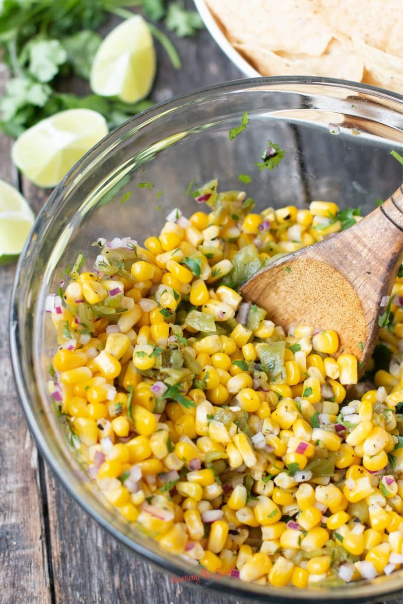glass bowl filled with Chipotle Corn Salsa and a wooden spoon to serve