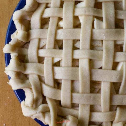 Easy Crisco Pie Crust Recipe used to make a lattice top pie in a blue pie plate.
