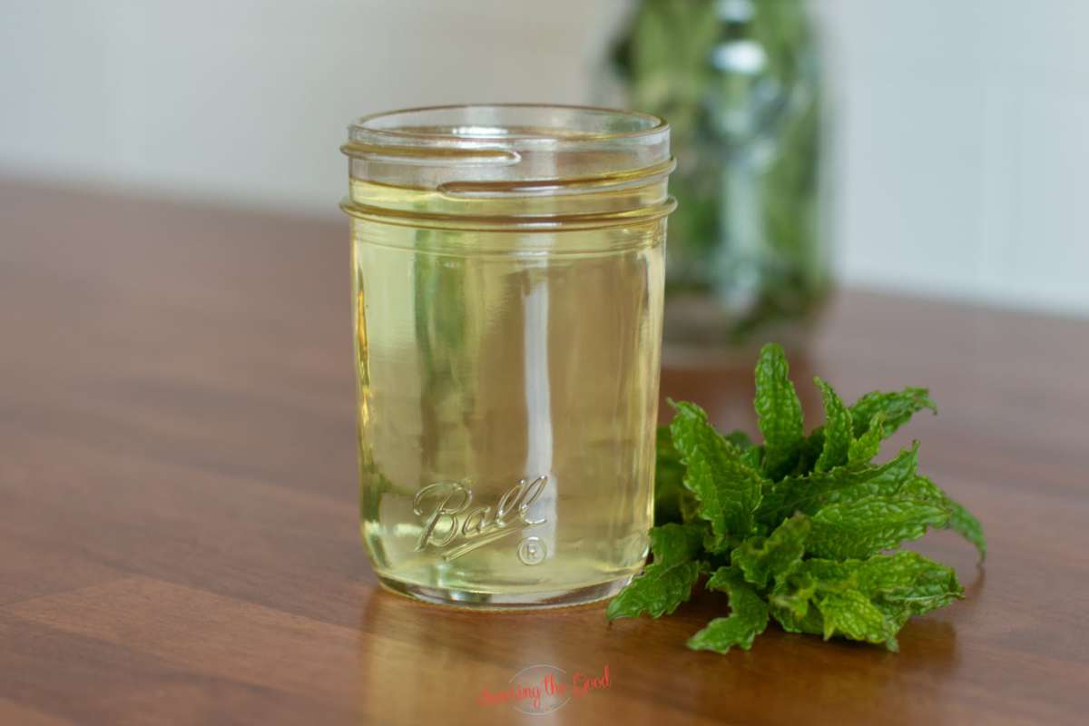 horizontal image of Mint Simple Syrup in a ball glass jar with mint on the countertop