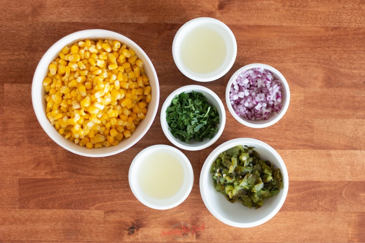 chipotle corn salsa ingredients in separate white bowls on a butcher block countertop