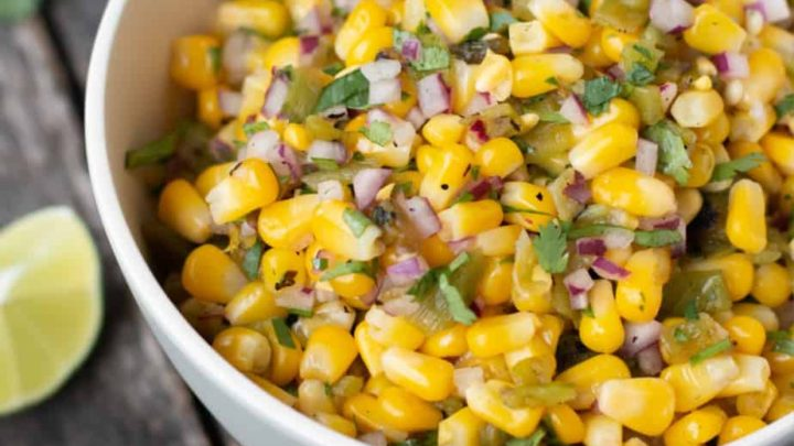 chipotle corn slasa in a white bowl showing texture of the salsa, limes in the background, square image
