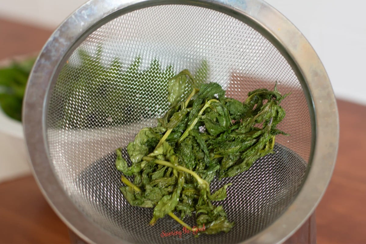 steeped mint in a mesh strainer