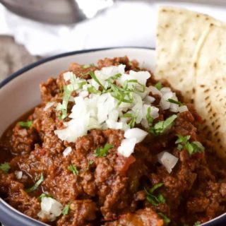 bowl of chili without beans garnished with chopped onions