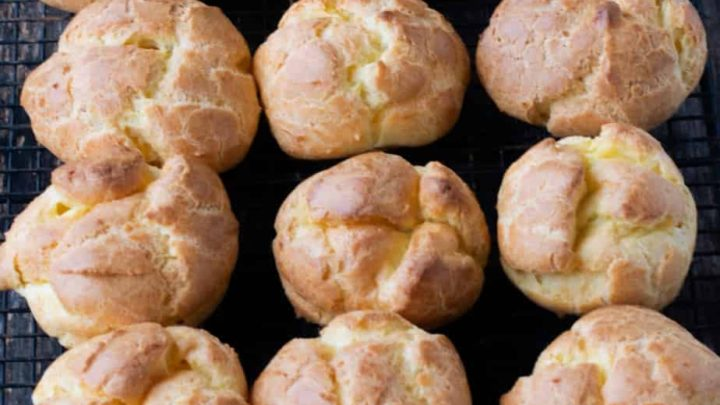 over a dozen golden brown choux pastry puffs closely spaced together on a cooling rack.