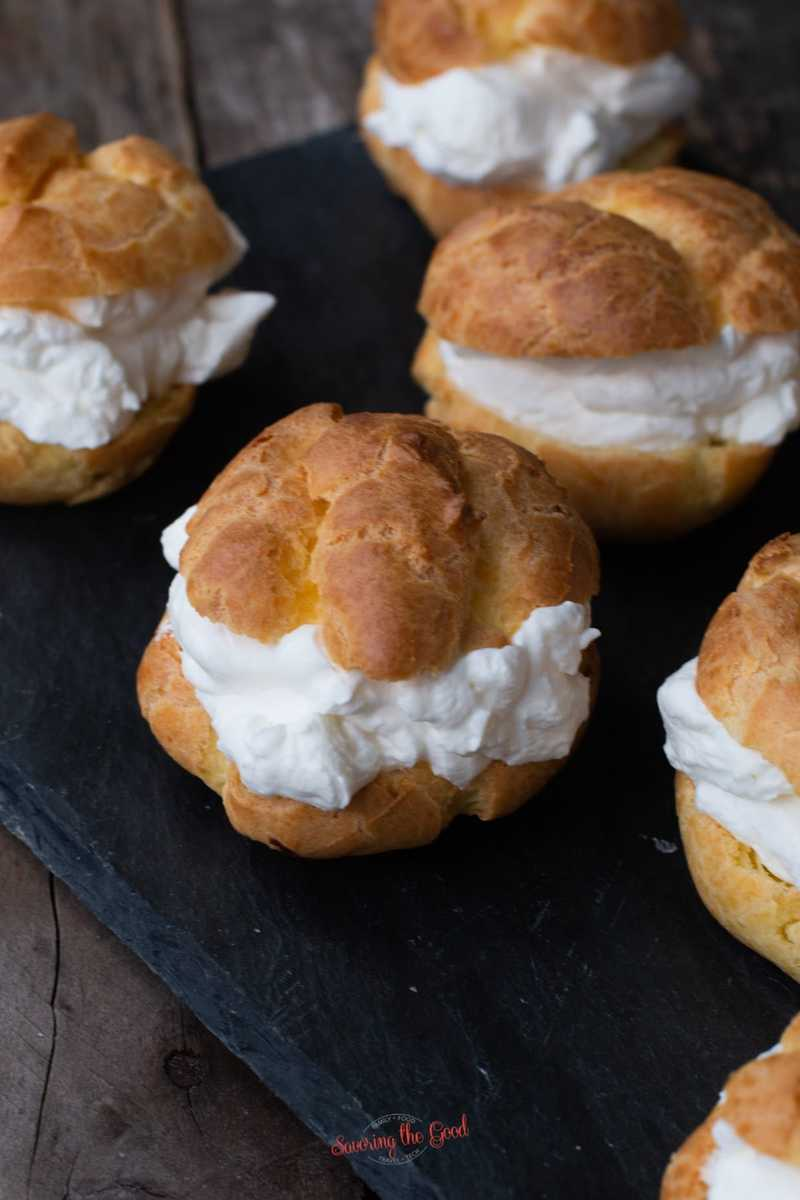 finished cream puffs lined up on a dark slate serving board