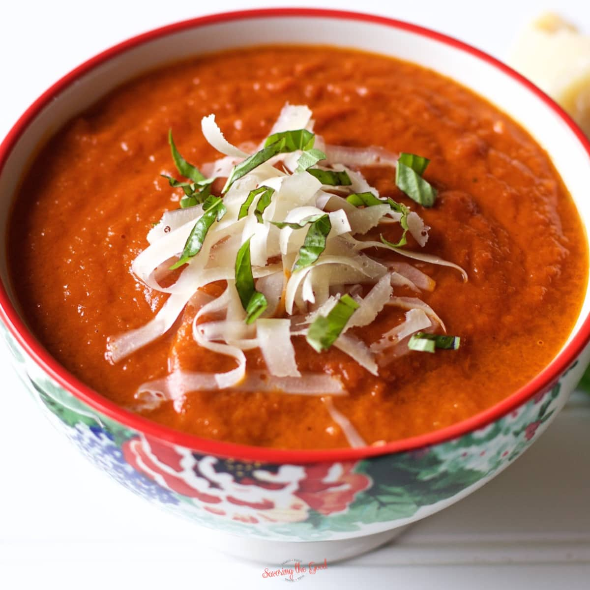 oven roasted tomato soup in a bowl with cheese and basil garnish, square image