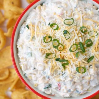 Easy Mexican Corn Dip in a red rimmed bowl with chips
