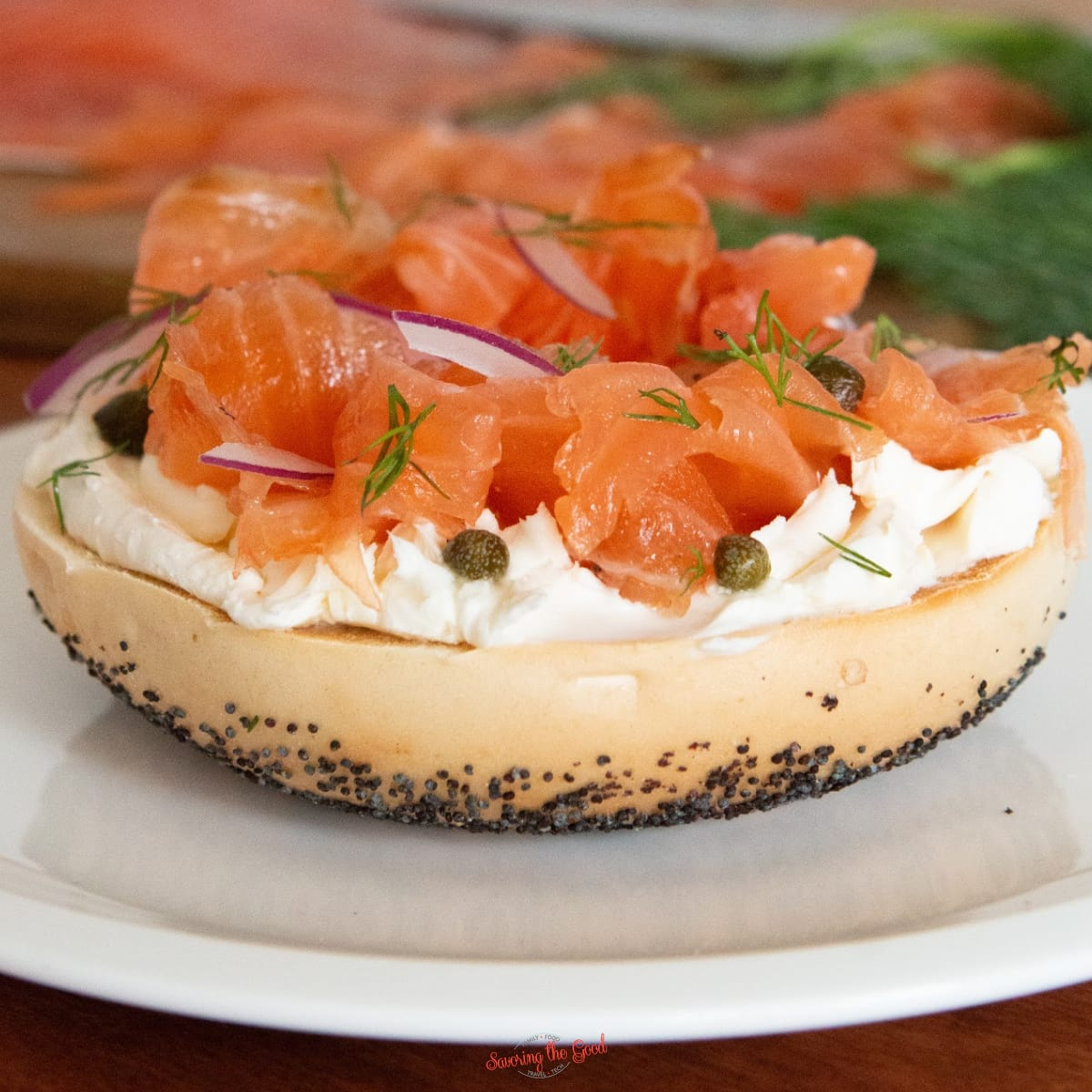 Salmon Lox Recipe featuring a toasted bagel, cream cheese, fresh dill, capers
