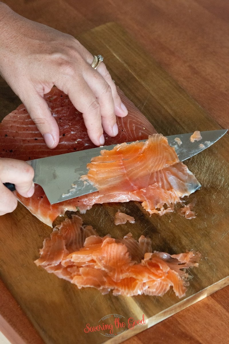 using a sharp knife to slice cured salmon