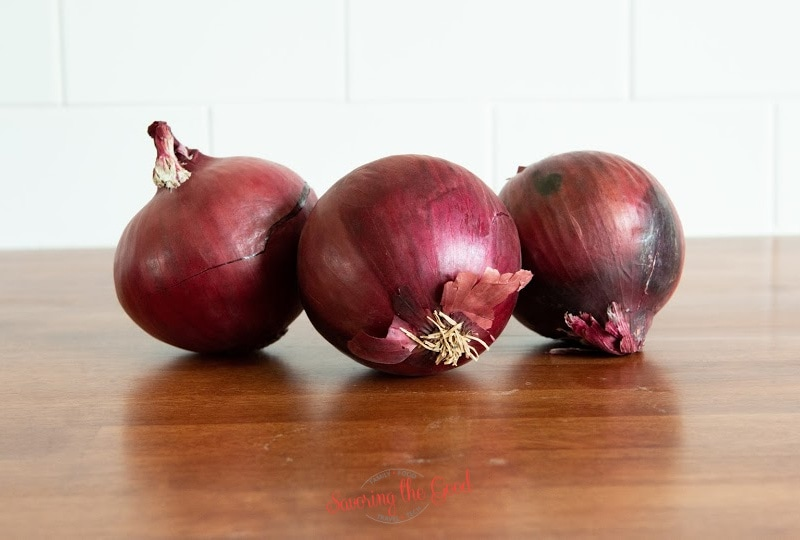 3 unpeeled red onions on a wooden cutting board