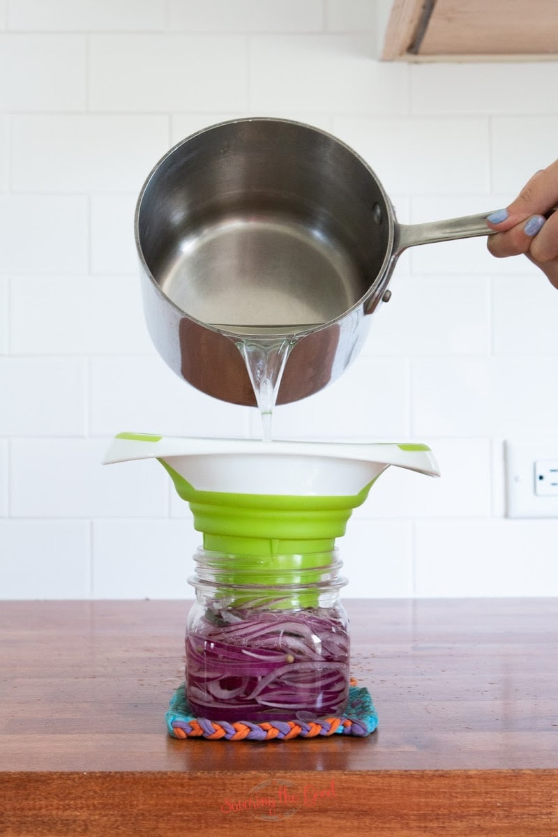 pouring vinegar mixture over red onions for Pickled Red Onion Recipe