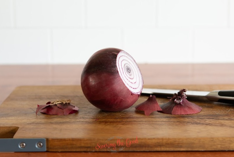 un peeled red onion on a cutting board