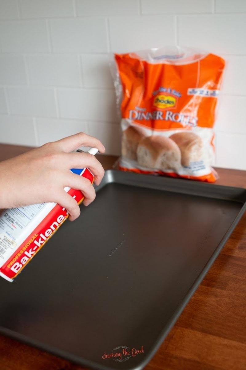 spraying a sheet pan with pan spray for baking Rhodes Rolls