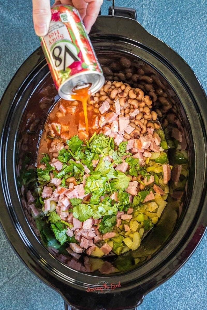 adding v-8 juice to a slow cooker to make Hoppin' John