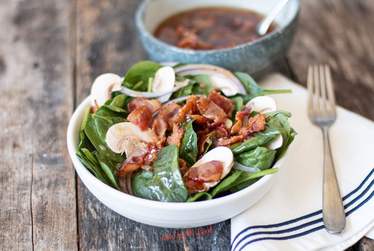 horizontal image of Hot Bacon Dressing on a spinach salad
