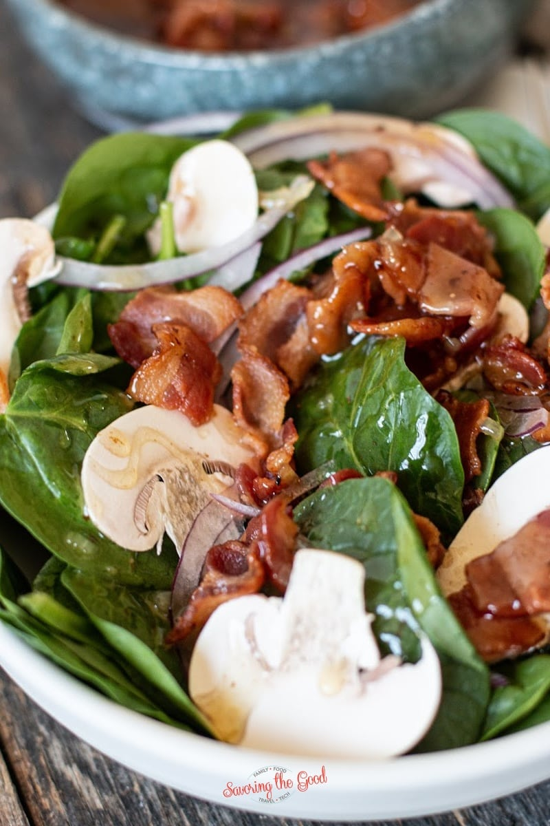 tight shot of Hot Bacon Dressing over spinach