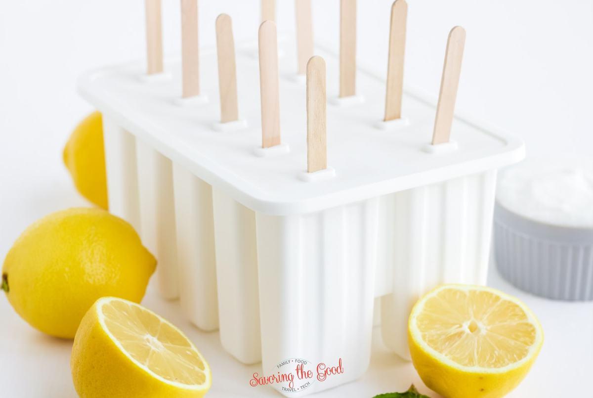 tray of Lemonade Popsicles in their molds, lemons as garnish