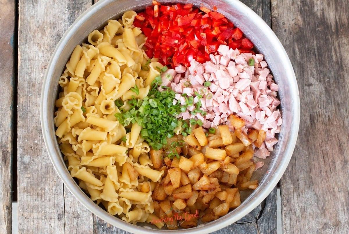Hawaiian pasta salad ingredients in a pot to be stirred horizontal image