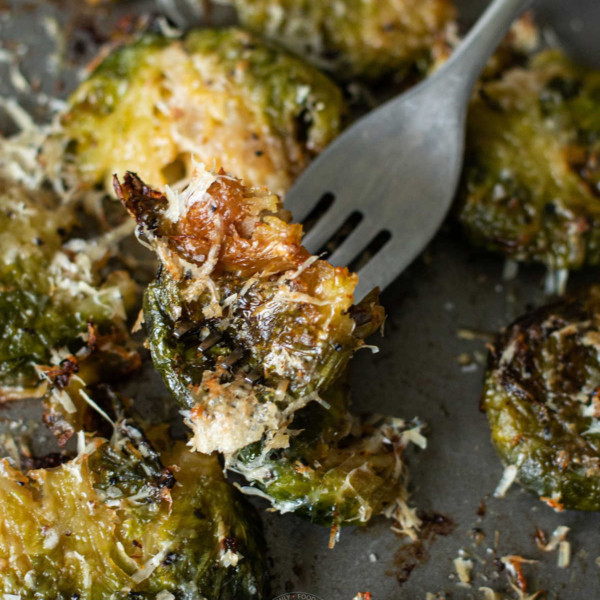 she pan of smashed Brussels sprouts with a fork picking up a single sprout showing texture