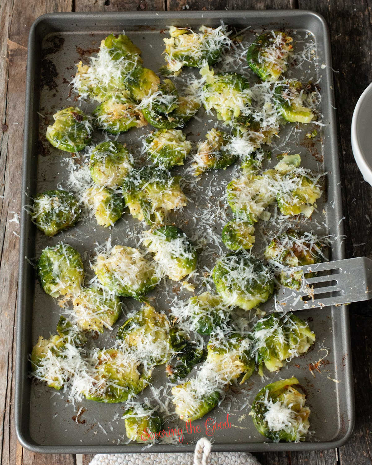 sheet pan with Parmesan cheese on Smashed Brussel Sprouts with a small spatula turning over one